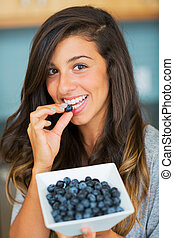 Beautiful woman eating blueberries, Healthy Food Lifestyle