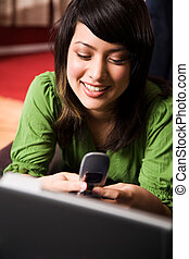 Asian girl relaxing and texting - A beautiful asian girl...