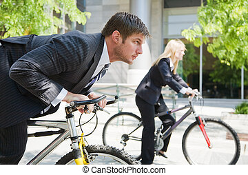 Business people racing on bicycles - Two business people...
