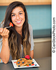 Woman eating Waffles with Fresh Fruit - Young woman eating...