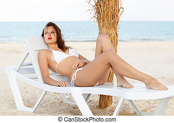 Pretty leggy woman in white swimsuit lying on the beach bed...
