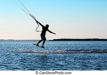 Silhouette of a kitesurfer jumping over the water