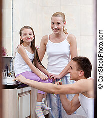 Family of three people brush their dents in bathroom