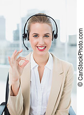 Smiling pretty call centre agent giving okay gesture -...