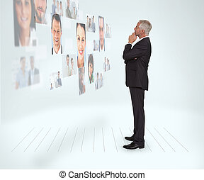 Thoughtful businessman looking at a wall covered by profile...