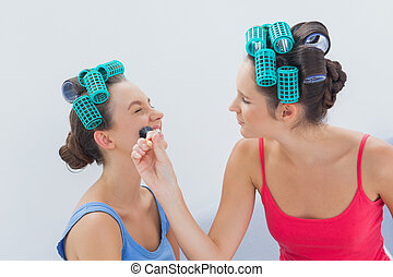 Friends in hair rollers having fun with makeup at sleepover