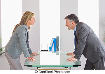 Two angry businesspeople arguing on each side of a desk -...