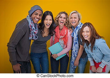 Cheerful group of friends laughing together on yellow...