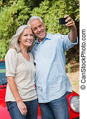 Smiling mature couple taking pictures of themselves leaning...