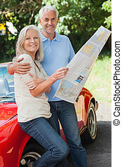 Happy mature couple reading map together by their cabriolet