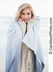 Smiling blonde woman covering herself in a blanket on the...