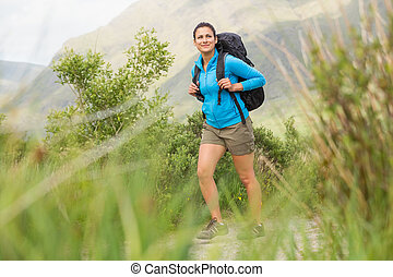 Female hiker with backpack walking and smiling