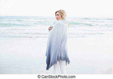 Pensive blonde woman warming herself in a blanket on the...