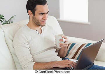 Calm attractive man drinking coffee while working on his...