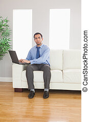 Stern young businessman using his laptop while sitting on...