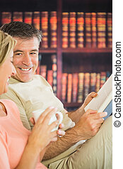 Happy mature couple sitting on a sofa in a reading room with...
