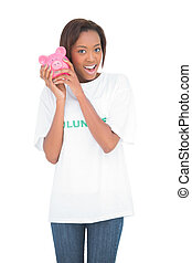 Smiling woman shaking piggy bank by her ear on white...