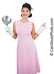 Cheerful black hair model holding a pan and wearing rubber...