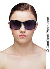 Serious young model wearing classy sunglasses on white...