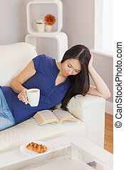Pretty young asian woman lying on the sofa reading a book holding her coffee in living room at home