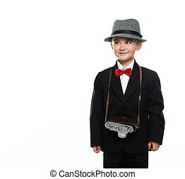 Little boy in hat and black suit with vintage camera...