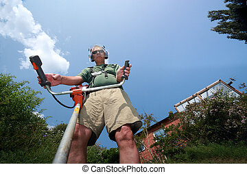 Adult man cutting wild grass - Adult man working with weeds...