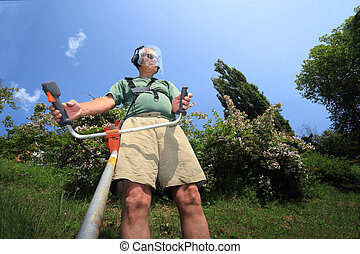 grass cutting man in action - Adult man working with weeds...