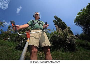 Man cutting wild grass under a blue sky - Adult man working...
