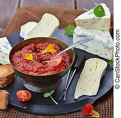 cheese plate with tomato chutney on the wooden table