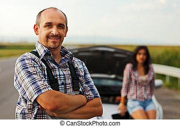 Repairman and woman driver in front of broken car