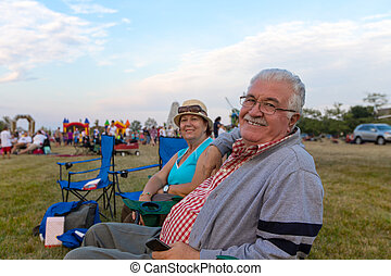 Elderly spectators sitting in deckchairs - Elderly couple of...