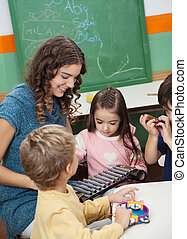 Teacher And Children Playing With Xylophone In Class
