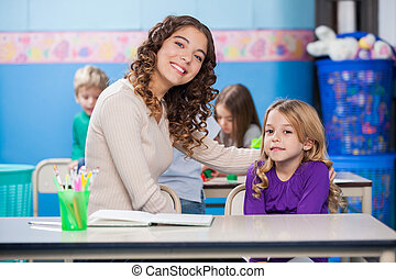 Teacher With Arm Around Little Girl In Classroom - Portrait...