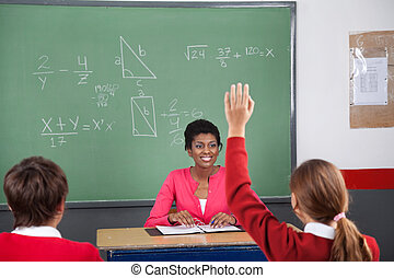 Teenage Girl Raising Hand While Teacher Looking At Her -...