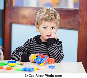 Unhappy Boy With Blocks In Classroom