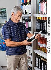 uomo, lettura, istruzioni, da, alcool, bottiglia