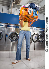 Woman Carrying Basket Of Dirty Clothes In Laundry - Young...