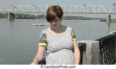 pregnant beautiful young woman by embankment, near the river...