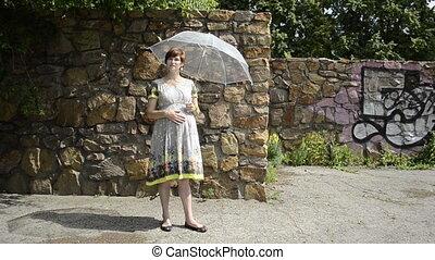 Young pregnant woman under umbrella