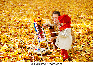 Mother and child drawing on easel in autumn park. Creative kids development concept.