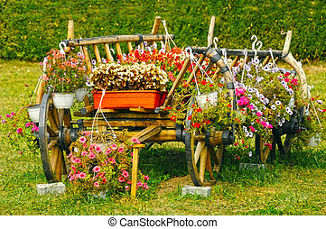 old wooden cart overflowing with red flowers