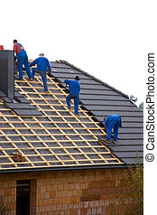 Roofers cover the roof of a house