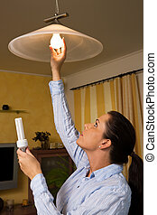 Young woman changes in energy-saving light bulb lamp