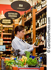 Purchases of wine at the supermarket - Young woman in a...