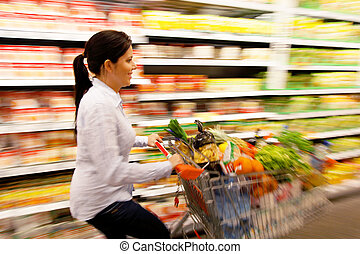 Woman with shopping basket in the supermarket - Young woman...