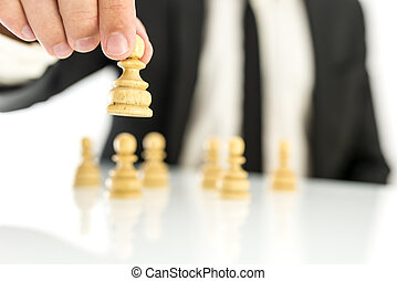 Business strategy concept - Businessman moving pawn chess...