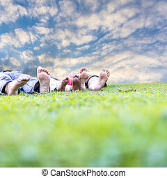 Family lying in grass - Young family with adopted child...