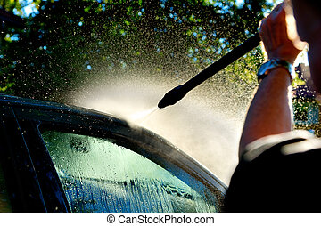 man washing car in sunshine with high pressure washer
