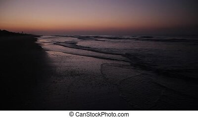Sea at Daybreak Loop - Waves break on a sandy beach just...