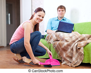 married couple at home - Woman sweeping the floor at home...